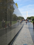 A view of the Vietnam Memorial wall with the Washington Monument in the background.